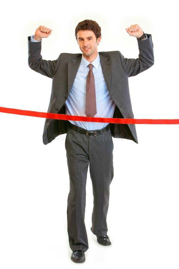 Pleased businessman crossing finish line stock photo