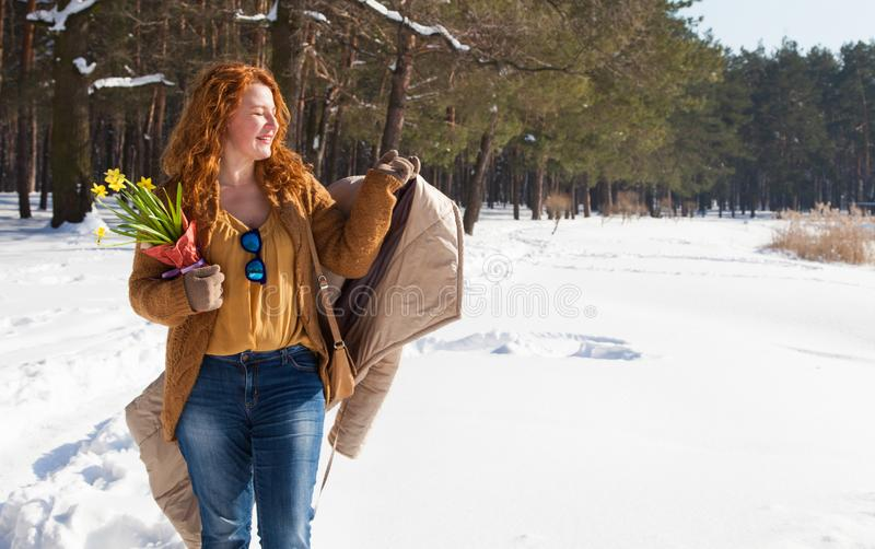 Pleased charming woman holding her coat in hand and relaxing while walking through snowdrifts royalty free stock photo