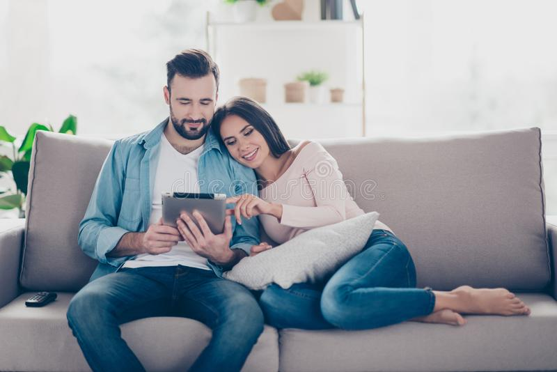 Pleased cheerful relaxed beautiful cute couple of lovers is buying ordering products on the internet and choosing furniture for t royalty free stock photo