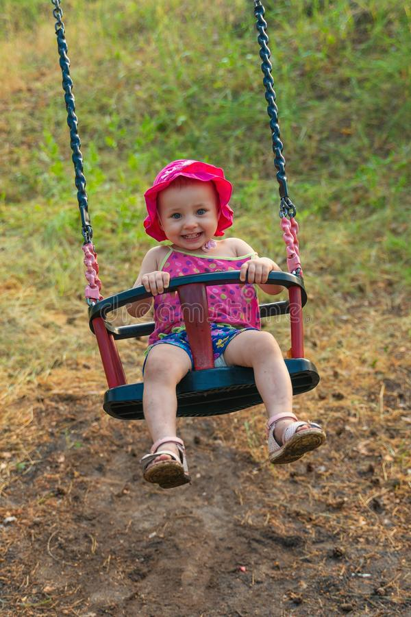 Pleased child on swing in summer season royalty free stock images