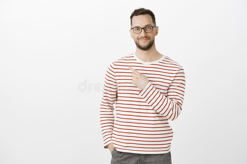 Pleased confident male model with bristle in stylish eyewear and casual clothes, pointing at upper left corner and stock photos