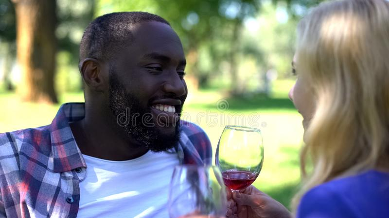 Pleased couple enjoying beverage on picnic, romantic date, wine traditions stock image
