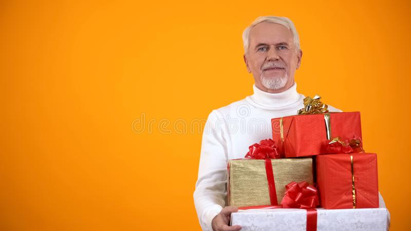 Pleased elderly male holding giftboxes and smiling, big discounts on holidays stock photo