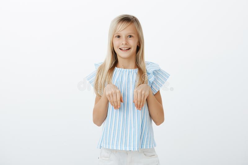 Pleased excited little female child with blond hair in trendy blue blouse holding palms over chest as if it is bunny. Paws, smiling broadly, feeling amazed stock photo