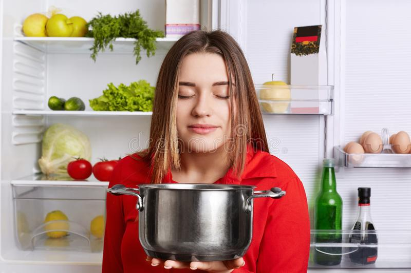 Pleased female holds saucepan, smells pleasant oudour, cooked delicious soup with vegetables, stands at kitchen near opened fridge stock image