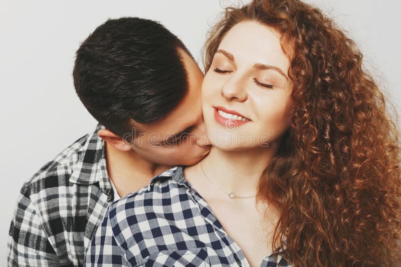 Pleased female keeps eyes shut as recieves passionate kiss in ne royalty free stock images