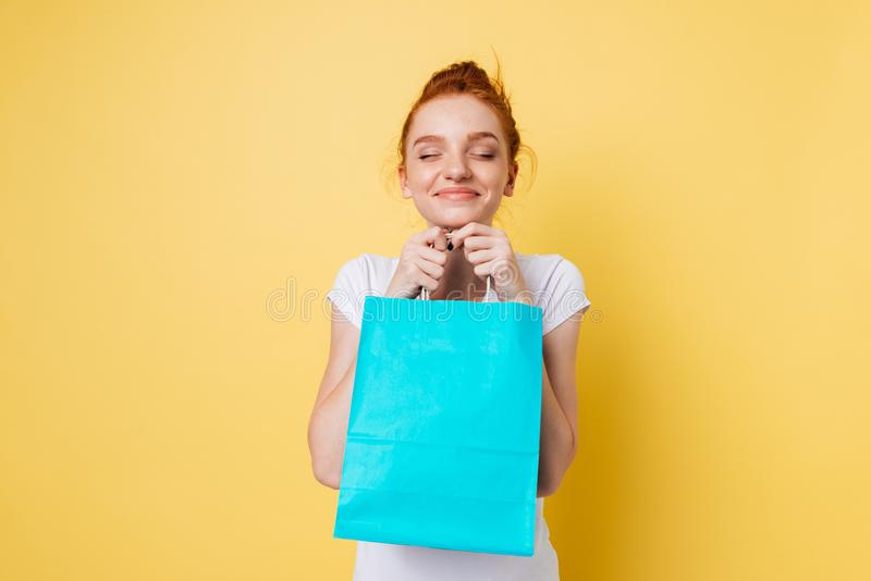 Pleased ginger woman holding packet in hands with closed eyes. Over yellow background royalty free stock images