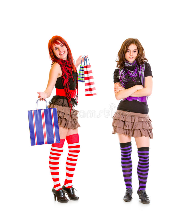 Pleased girl showing bags to her sad girlfriend. Pleased pretty girl showing shopping bags to her sad girlfriend isolated on white royalty free stock image