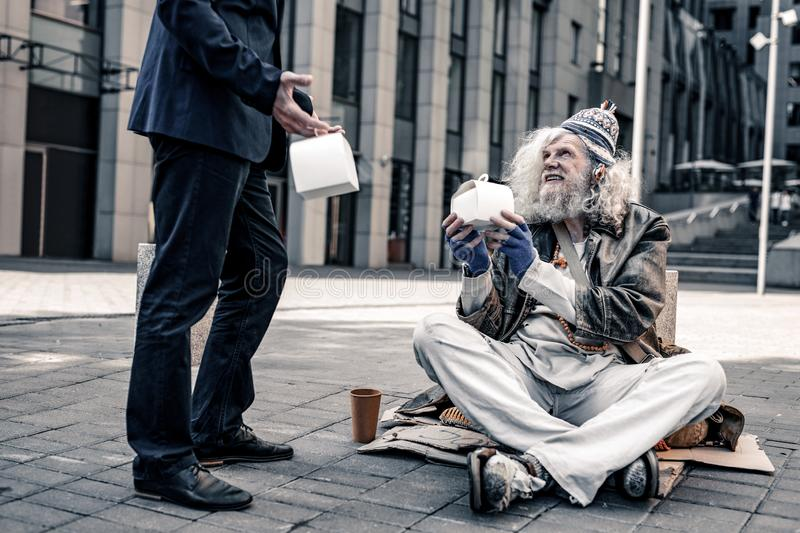 Pleased grey-haired senior homeless sitting covered in rags stock photo