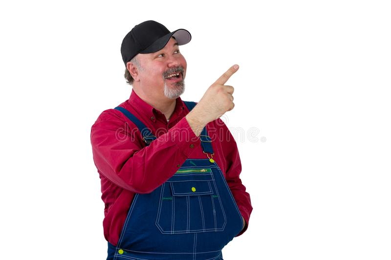Pleased happy man in denim dungarees pointing up stock images