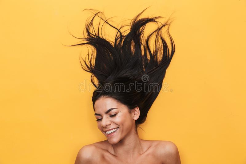 Pleased happy young woman lies isolated on yellow background. Healthy hair concept royalty free stock photography