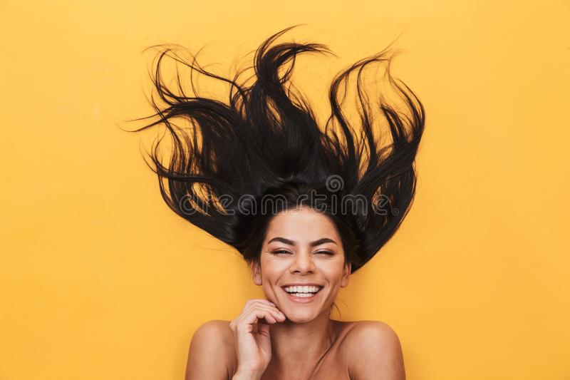 Pleased happy young woman lies isolated on yellow background. Healthy hair concept stock photography