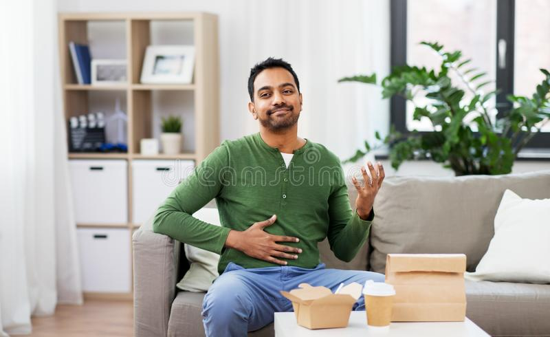 Pleased indian man eating takeaway food at home. Consumption and people concept - full and pleased indian man eating takeaway food at home stock photo