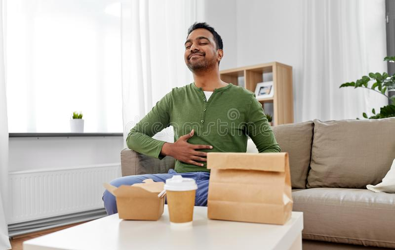 Pleased indian man eating takeaway food at home. Consumption and people concept - full and pleased indian man eating takeaway food at home stock images