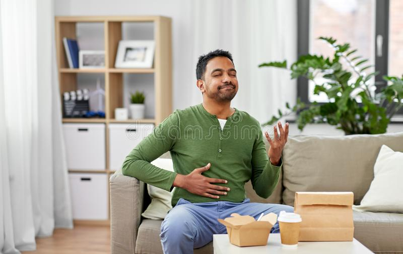 Pleased indian man eating takeaway food at home. Eating, consumption and people concept - full and pleased indian man enjoying takeaway food at home stock photography