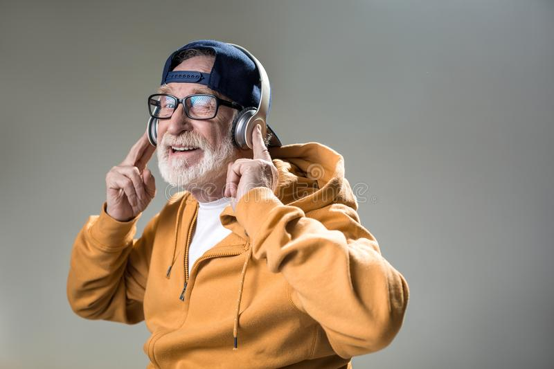 Pleased male pensioner resting to the tune stock photography