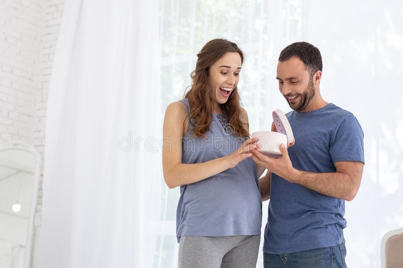 Pleased man giving gift to pregnant woman stock image