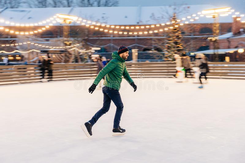 Pleased man in green jacket, wears skates, goes skating on ice, stock photography