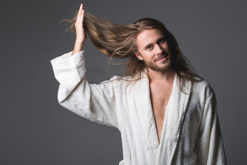 Pleased man holding up topknot. Waist up portrait of joyful guy in soft housecoat raising his long hair with one hand. He is looking at camera with light smile stock photos