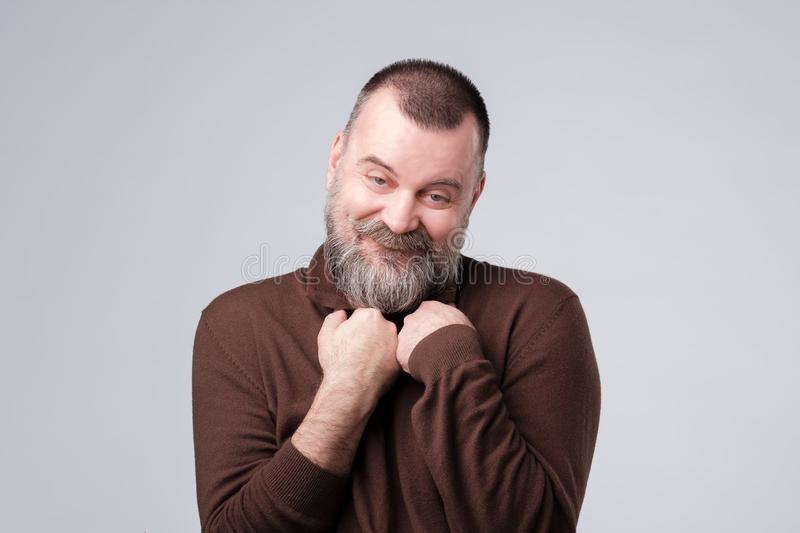 Pleased mature man glad to recieve compliment stock photos