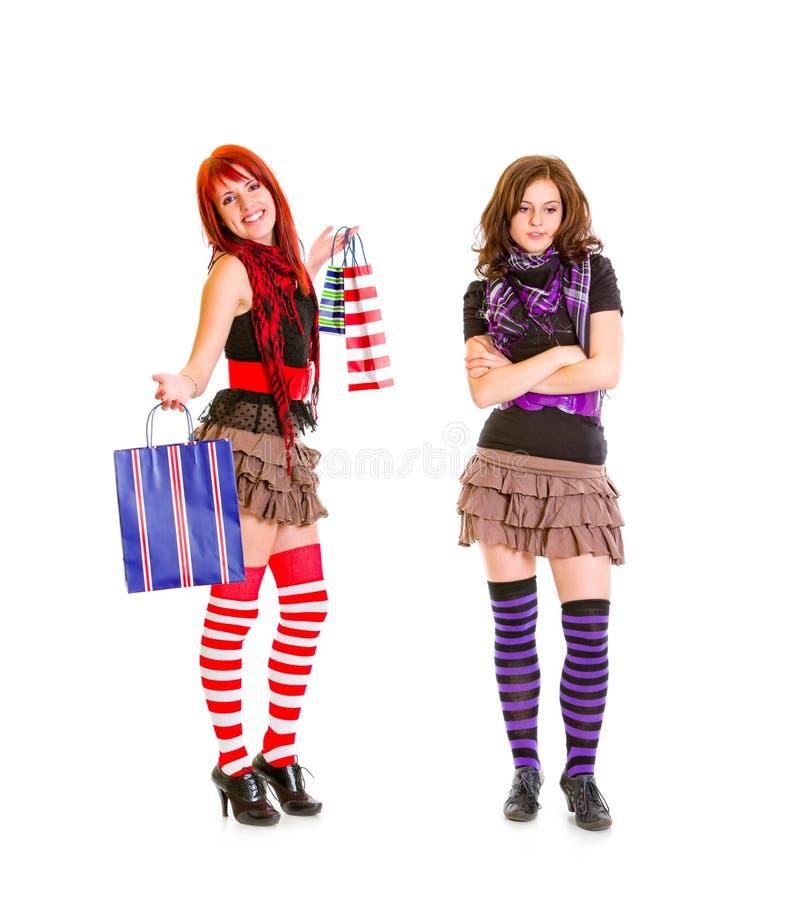 Pleased meisje dat zakken toont aan haar droevig meisje royalty-vrije stock afbeelding