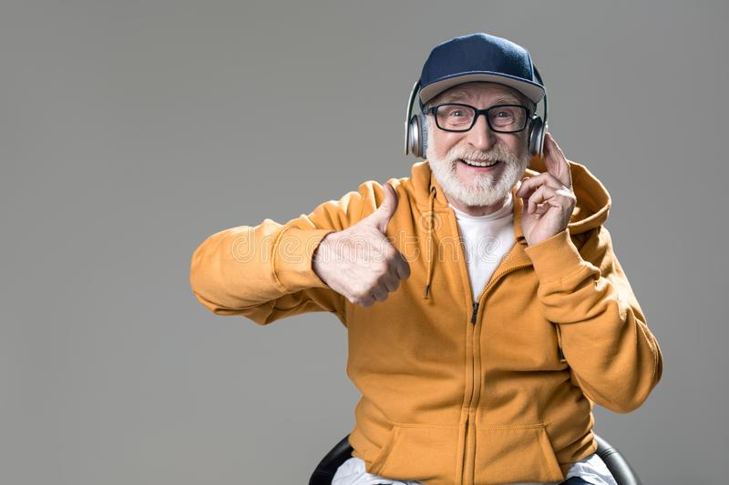 Pleased old man listening to lovely music stock photography