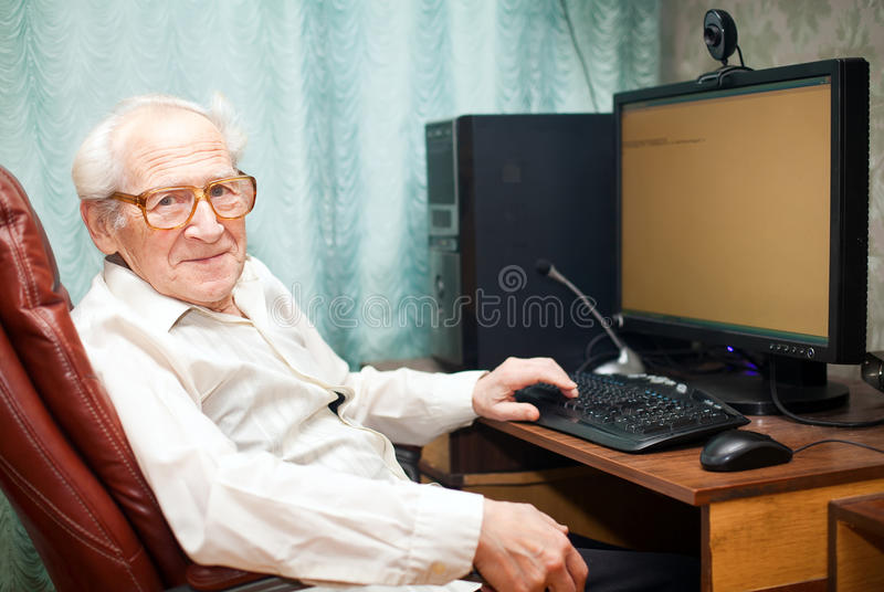 Pleased Old Man Near Computer. Smiling pleased old man sitting near computer - he is working royalty free stock photos