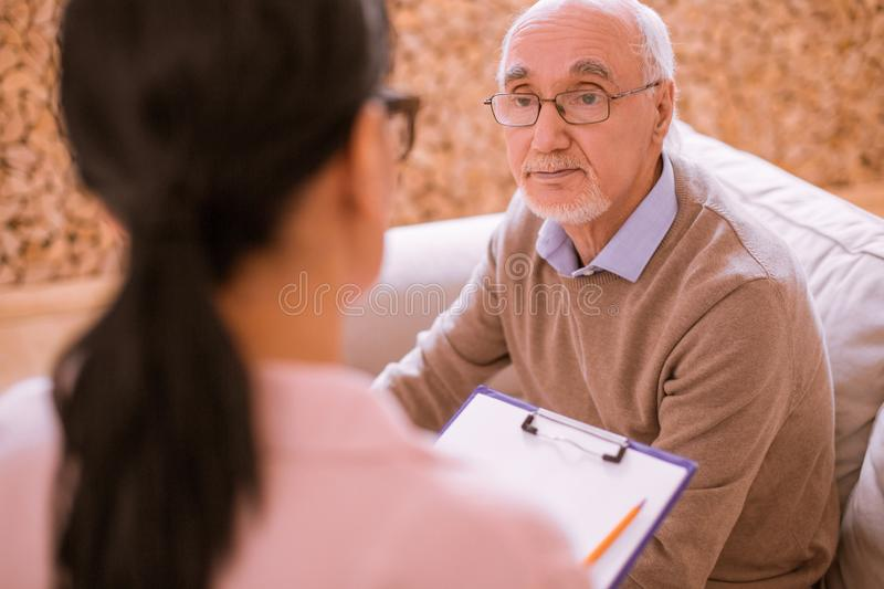 Pleased senior male person looking at his volunteer stock image