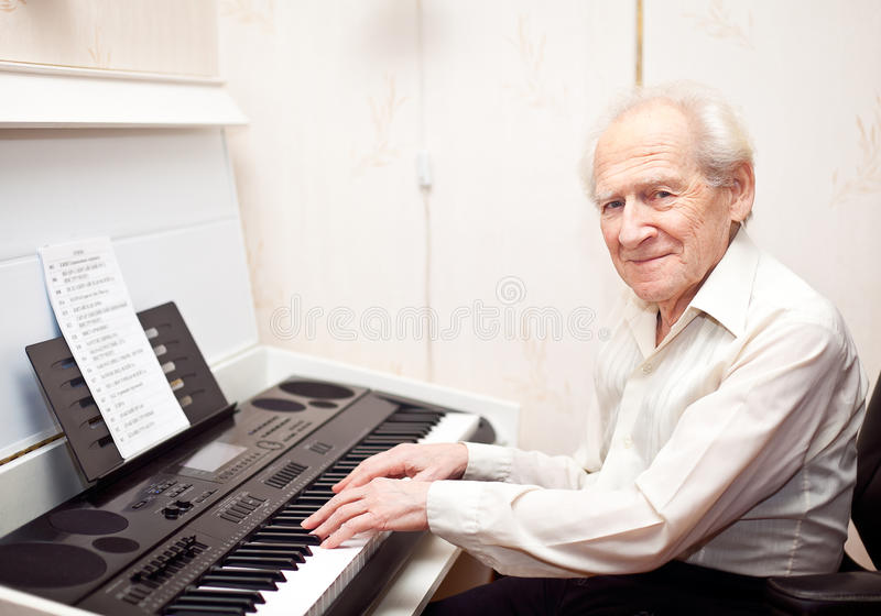 Pleased Senior Man Playing Piano stock photo