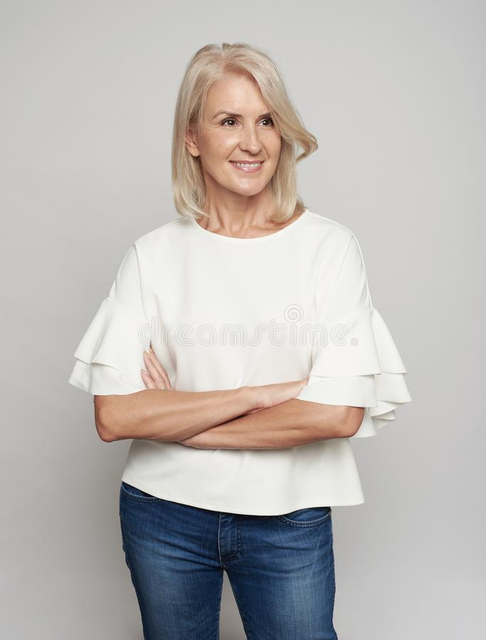 Pleased senior woman with crossed arms looking away stock photography