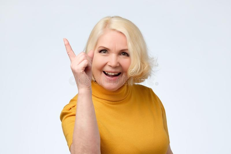 Pleased senior woman warning you giving advice stock photos