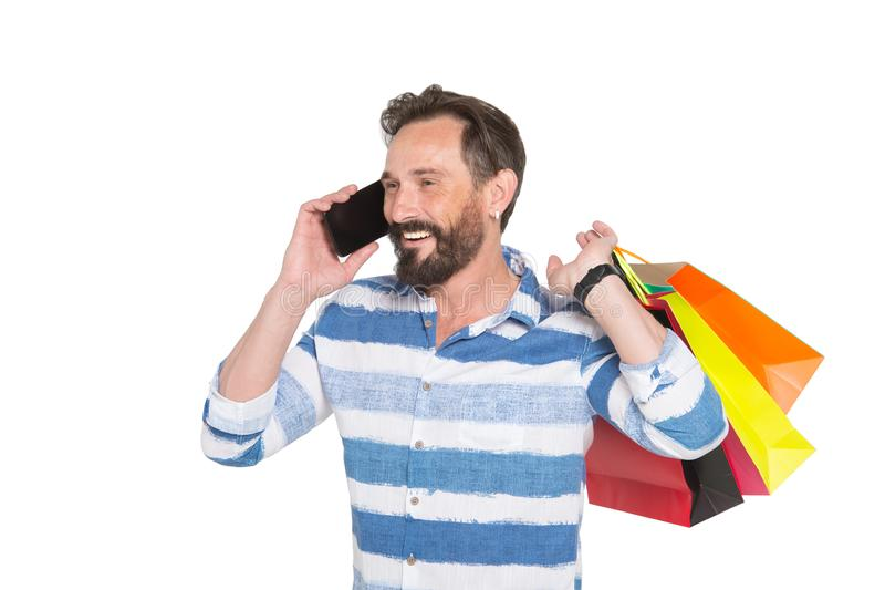Pleased shopaholic man sharing his shopping emotions while talking on mobile phone royalty free stock images