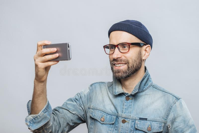 Pleased smiling bearded male with happy expression poses at came royalty free stock photo