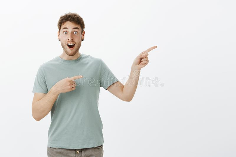 Pleased surprised attractive guy with fair hair, dropping jaw while discussing something amazing, pointing right with royalty free stock photography