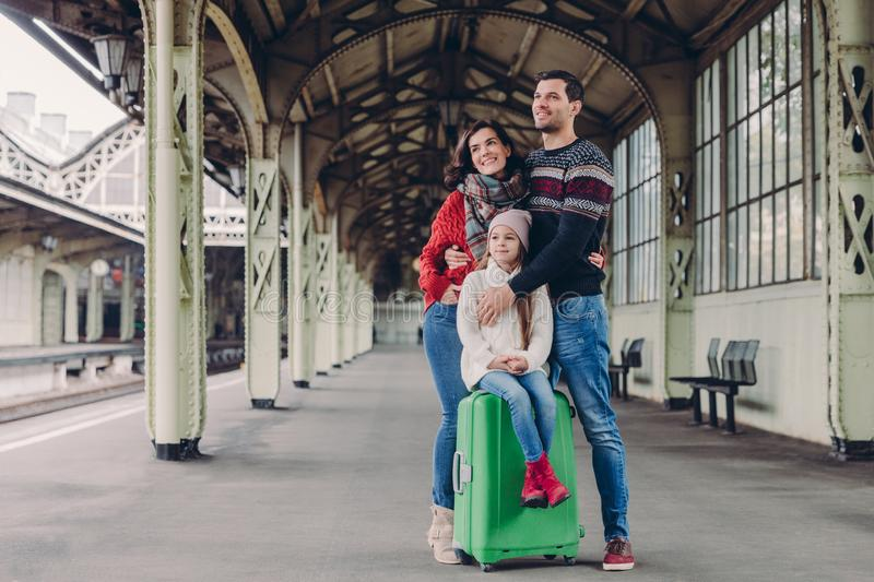 Pleased wife and husband cuddle with love, their daughter sits at suitcase, pose together on platform, look in ditance, wait for stock photos