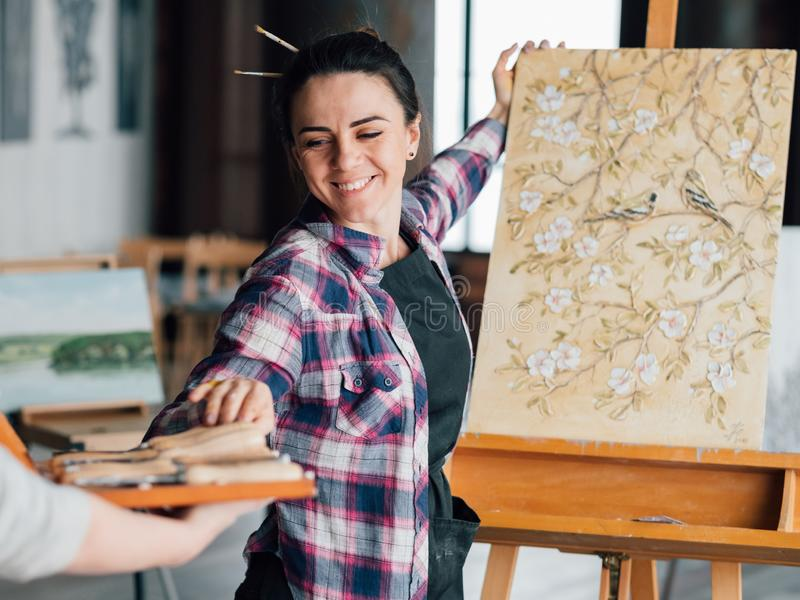 Pleased woman artist painting help assistance royalty free stock images