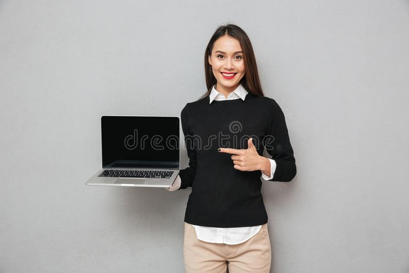 Pleased woman in business clothes showing blank laptop computer screen stock photos