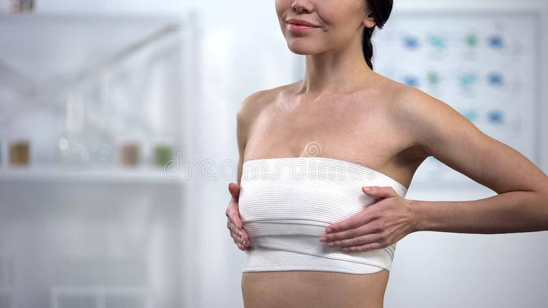 Pleased woman in elasto-fit compression enjoying result of mammoplasty, surgery. Stock photo stock photos