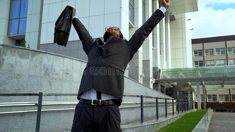 Pleased with work results businessman standing with hands up, successful deal. Stock photo royalty free stock images