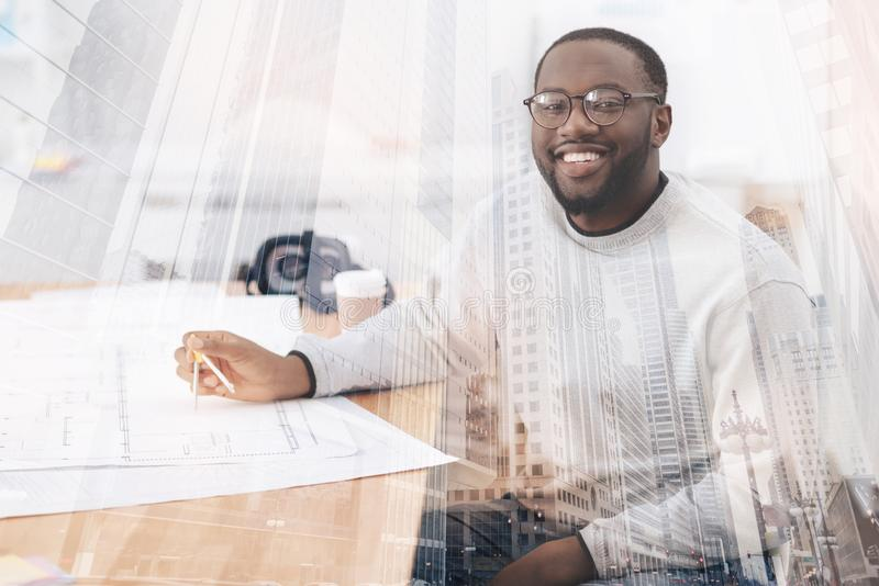 Educated young man using compasses. Pleased with work. Young educated African American sitting at the table while using compasses and smiling at you stock photos