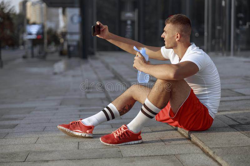 Pleased young Caucasian sportsman taking a selfie stock photography