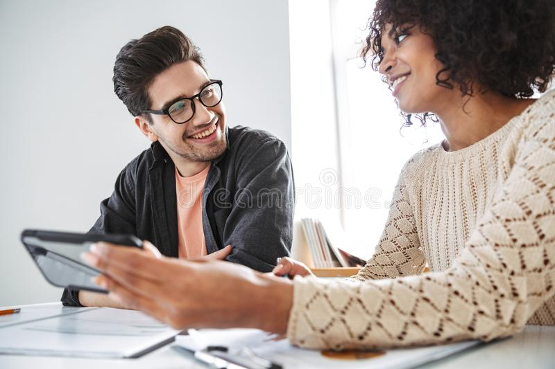 Pleased young colleagues using smartphone together royalty free stock photos