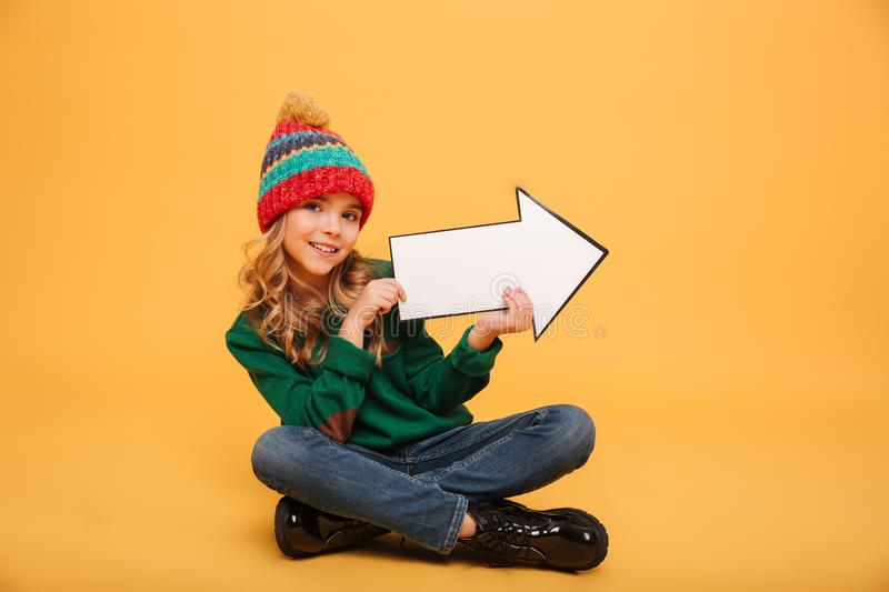 Pleased Young girl in sweater and hat sitting on floor stock image