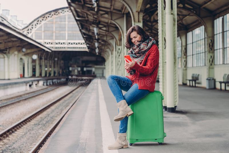Pleased young woman has positive look, sits crossed legs at bag, holds cell phone, searches place on online map, makes video call stock photo