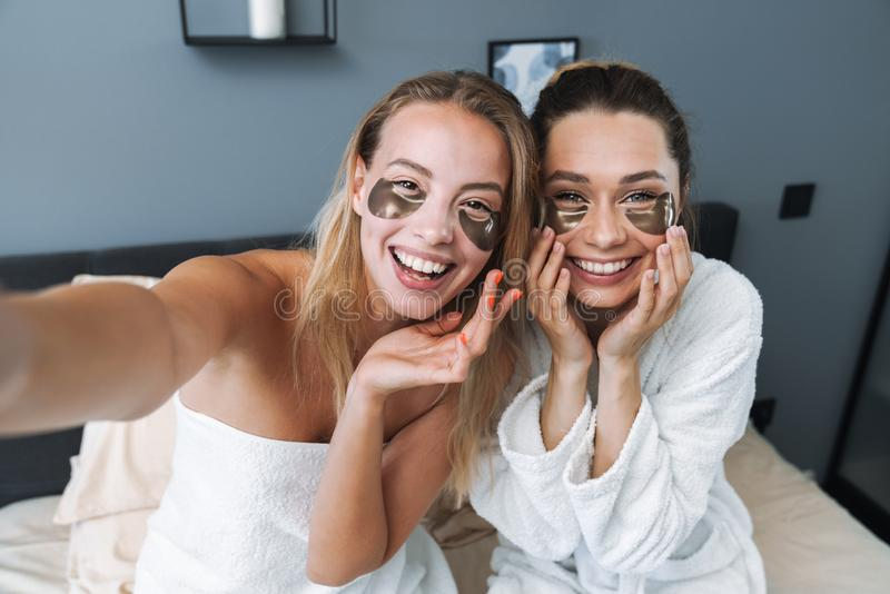 Pleased young women taking care of their skin with under eye patches royalty free stock photo