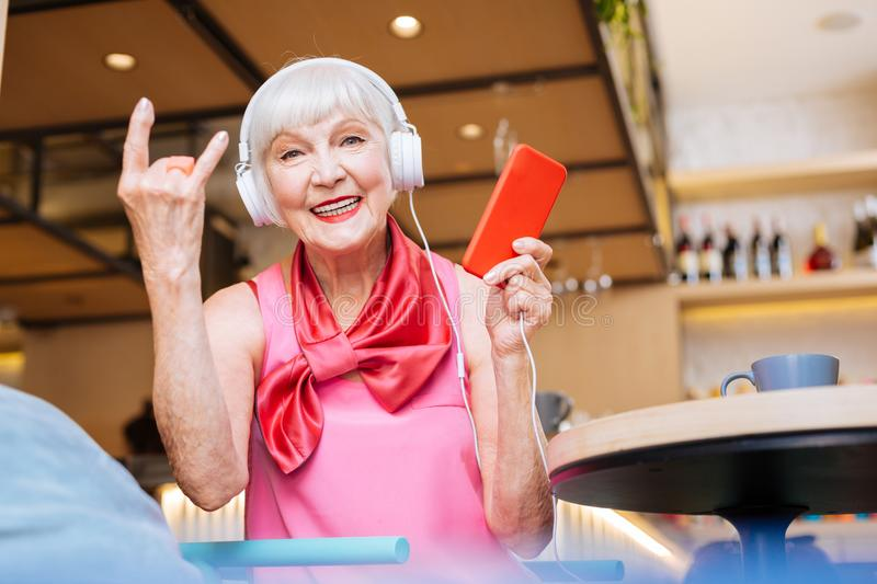 Positive nice woman sitting in the cafeteria. Pleasurable time. Positive nice woman listening to rock music while sitting in the cafeteria royalty free stock photo