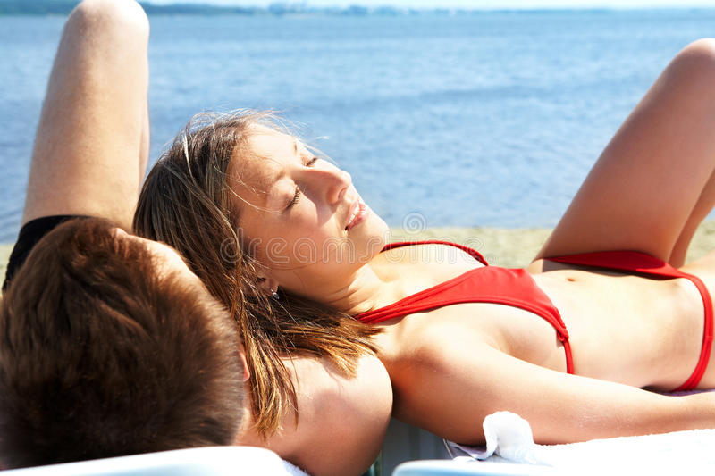 Pleasure. Image of two people lying on deck chairs and sunbathing on resort royalty free stock image