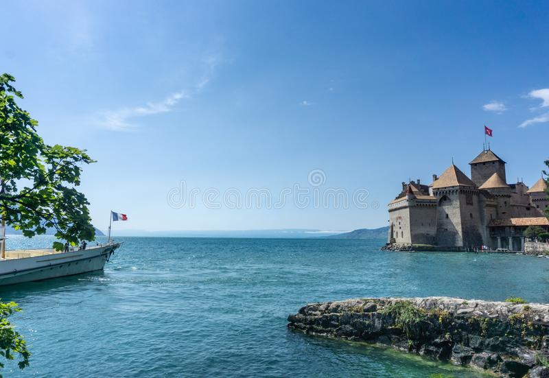 View of town  at Lake . A pleasure boat approaches the famous tourist site. Cloudless blue sky, blue water. Great trip . Chateau de Chillon at Lake Geneva stock image