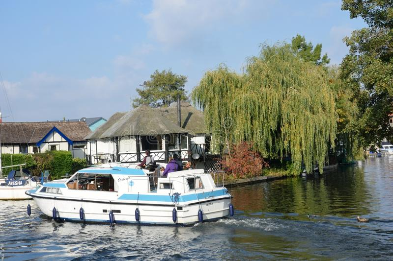 Pleasure boat on River Yare centre for tourism on Norfolk Broads with house in background. Wroxham Norfolk , United Kingdom - October 25, 2016: Pleasure boat on royalty free stock images
