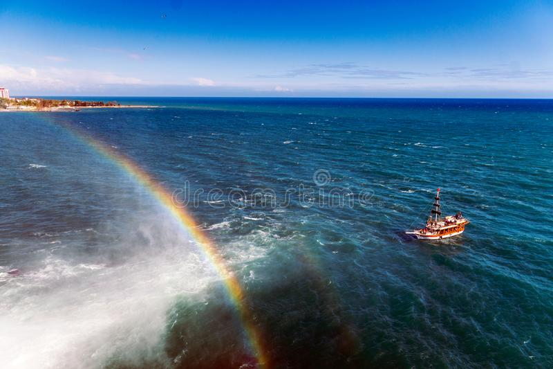 Pleasure boat in the sea near the shore with a waterfall and a rainbow stock photos